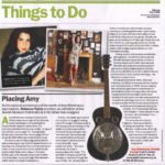 A newspaper article with two pictures of a girl with long dark hair, a picture of a guitar and text in green and black