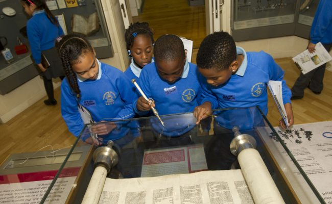Children in blue sweaters looking at open Torah in a glass case