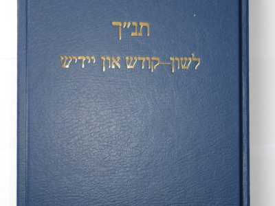 Blue book with Hebrew writing which says: Torah, prophets, writings. Tenakh. In the Holy Language and Yiddish.