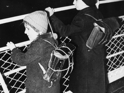 Small children in dark wool coats, hats and leather backpacks looking over the side of a railing