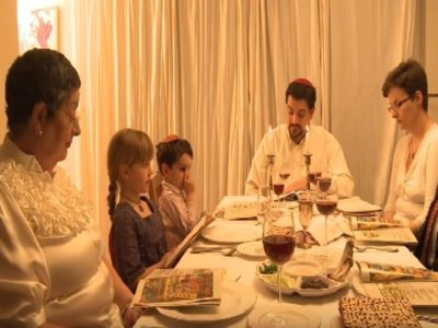 Family around a table set for Passover with Matzah