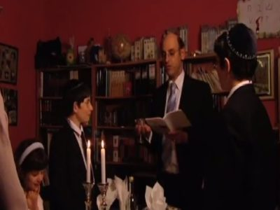 Father, two sons and daughter gathered around Shabbat table with two candles visible