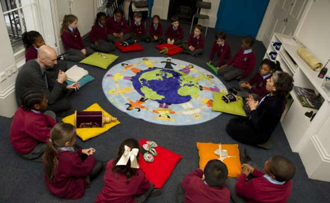 Children and educator sat in circle on coloured cushions with world rug in centre