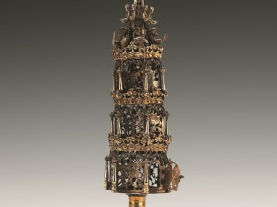 Silver three tiered spice box with floral designs and 6 figures from synagogue on top, steeple with ball and flag on top