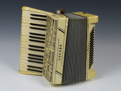 Black and white accordion, piano style keys on left, black buttons on right