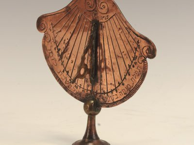 Gold fan shaped sundial on a stand with circular base