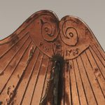 Close up top of sundial with Date and City and sprial imagery