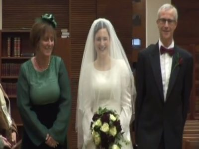 Woman in wedding dress and veil walking down aisle with parents on either side