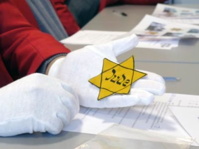 White gloved hand holding yellow star with Jude written on it in Hebrew style letters