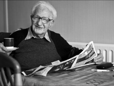 B & w photo of man in glasses sitting at table with newspaper