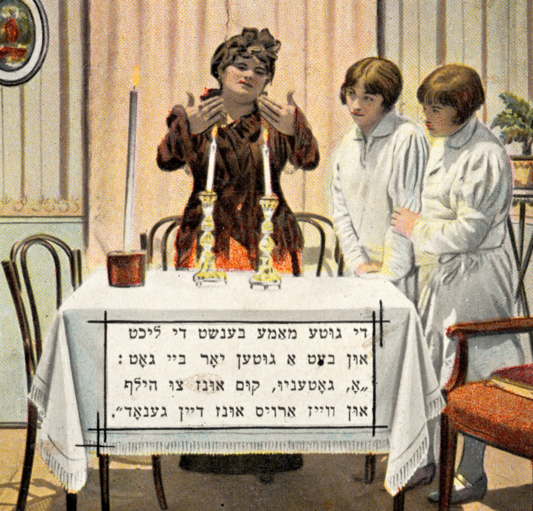 woman in brown standing in front of table with ttwo lit candles ready for Shabbat