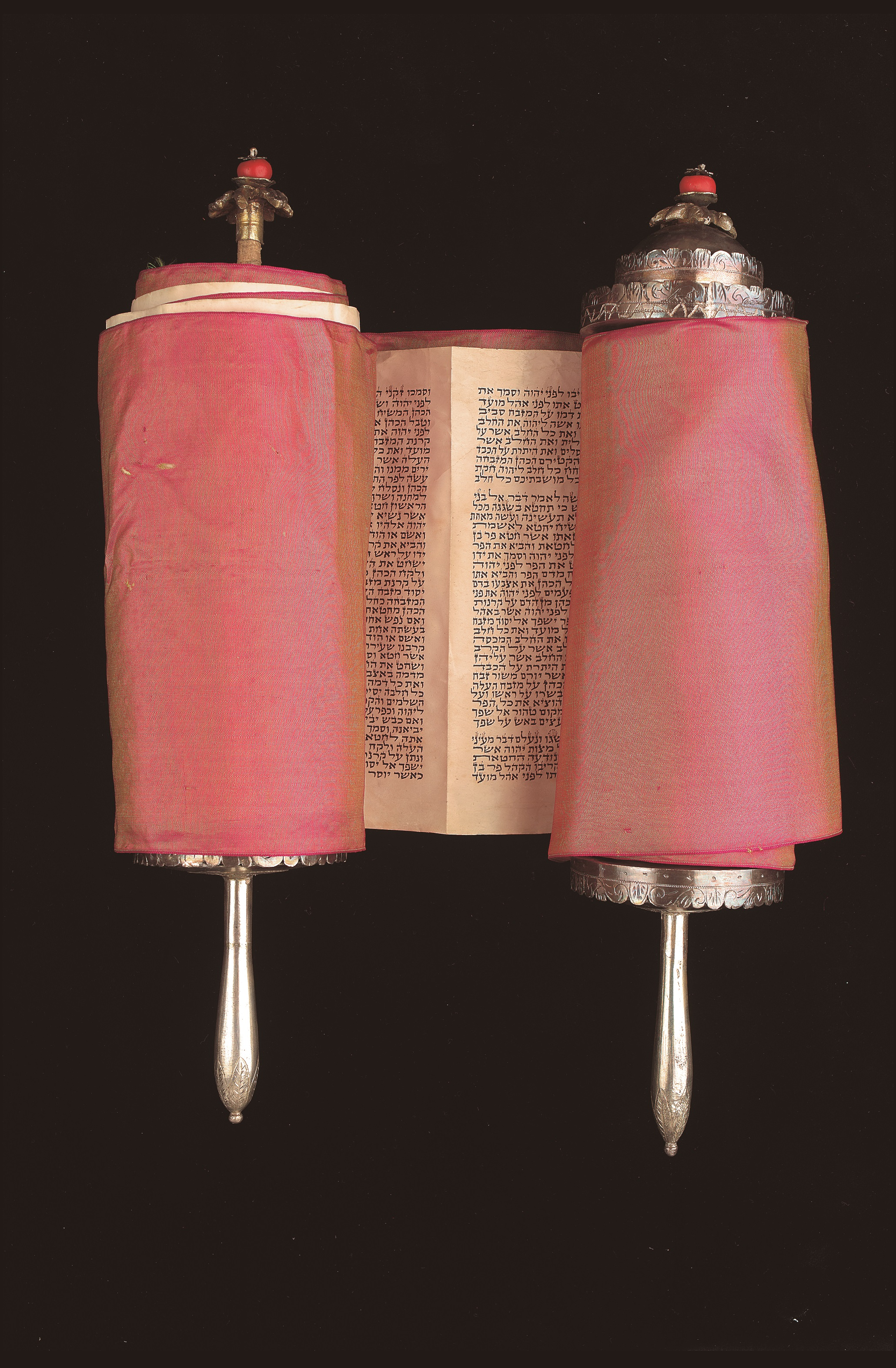 Torah scroll with silver rollers and red cloth covered etz chayim, hebrew text visible