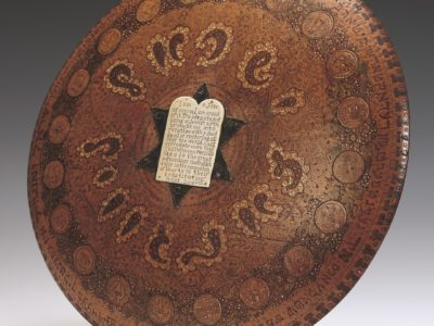 Wooden, circular plate with a white stone tablet on a black star of David in the centre.