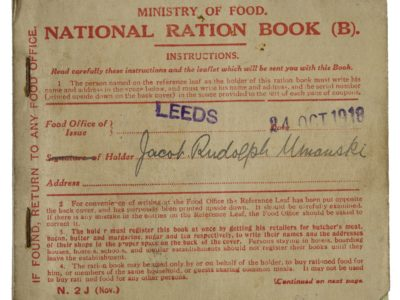 A small brown ration book with red writing.