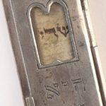 Close up of window with Shaddai in Hebrew visible on parchment