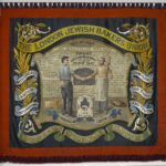 A red banner showing two bakers shaking hands in front of an oven. Above them are the words 'The London Jewish Bakers Union'.