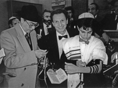A black and white photograph of a boy laying Tefillin at his Bar Mitzvah