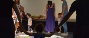 Small children and parents standing in a circle around a colourful playmat.