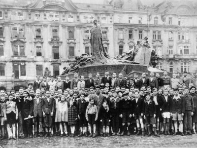 A black and white photograph of 300 children standing in an old town square.