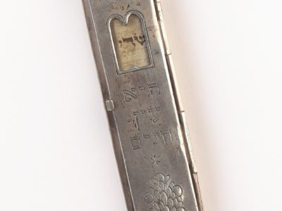 Silver case featuring a tablet shaped window that shows the Mezuzah scroll inside. On the scroll is written 'Shaddai' in Hebrew.