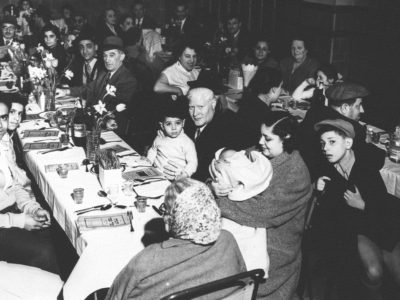 A black and white photograph showing people sat at two long tables
