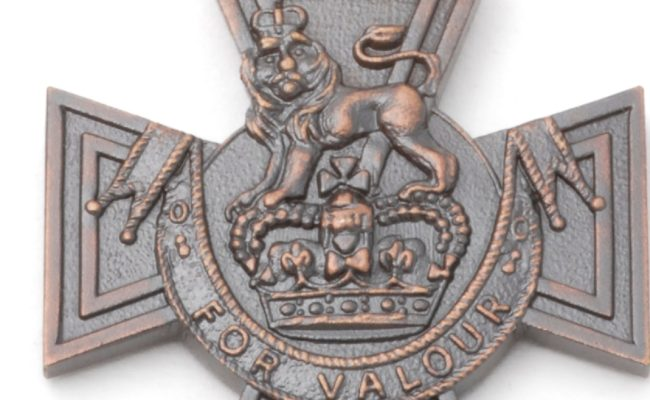 Bronze Victoria Cross with a lion and crown on it with a red ribbon