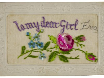 A white postcard with embroidered writing and flowers.