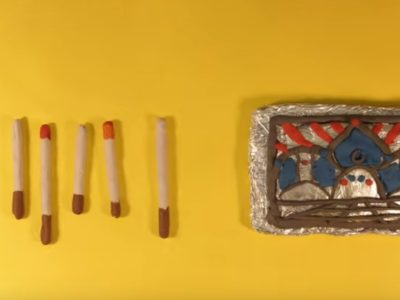 Clay model cigarette tin and clay cigarettes against a yellow background