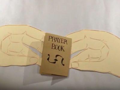 Brown model cardboard prayer book in between a drawing of two hands
