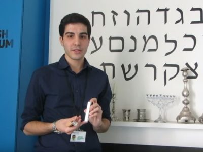 Intern holds silver mezuzah in hands