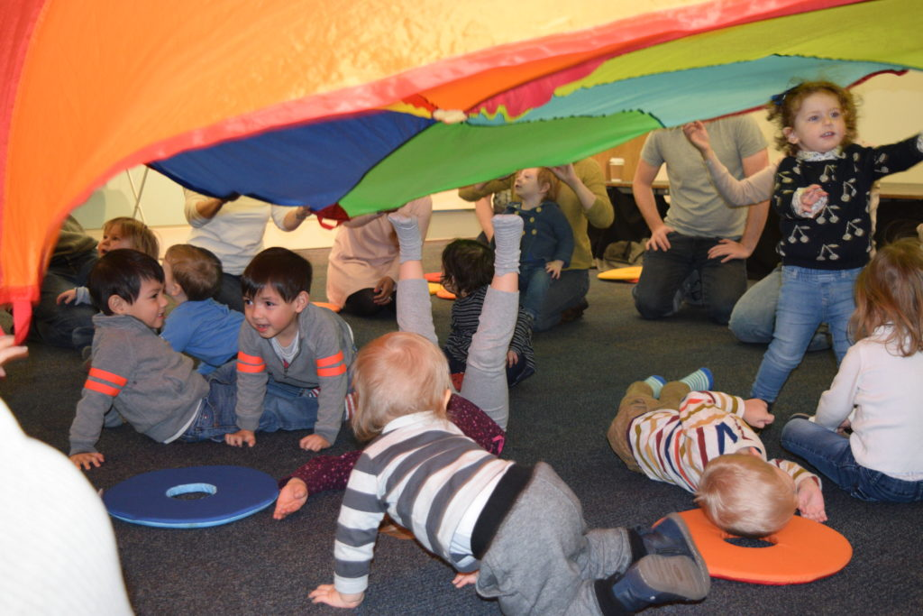 children crawling under colourful parachute
