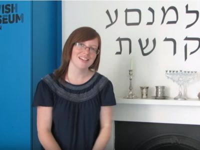 Intern stood in front of Hebrew lettering