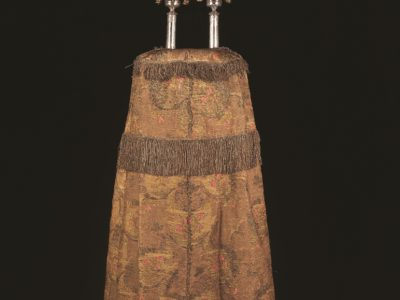 Picture of a large cloth cover to put on a Torah scroll, with rods with silver bells on top.