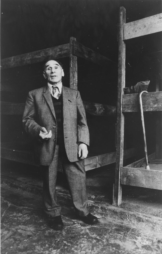 An elderly man - Leon Greenman - standing in front of bunk beds with walking stick hanging off the edge of one bunk