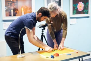 A dark haired man and a blonde woman filming their clay model on a wooden table.