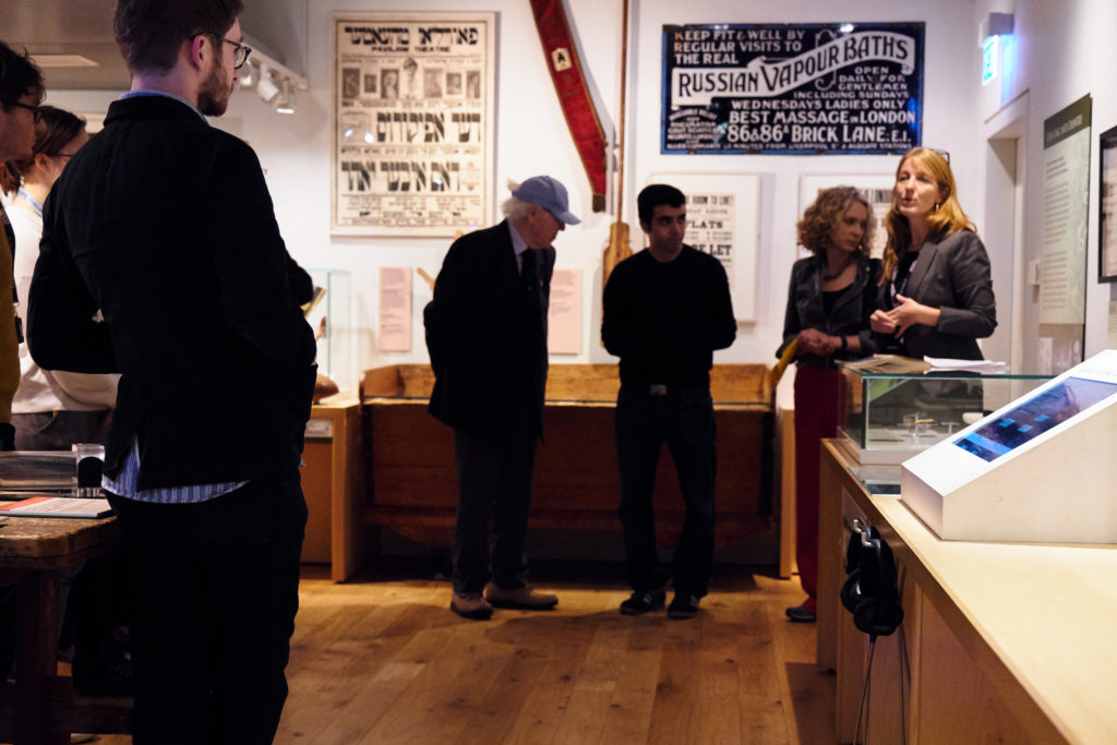 Curator giving a tour in the history galleries at the Jewish Museum London in front of a Russian Vapour Baths sign from London's East End