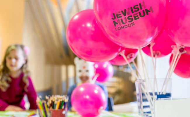 Pink balloons with Jewish Museum London logo in foreground and children doing crafts in the background