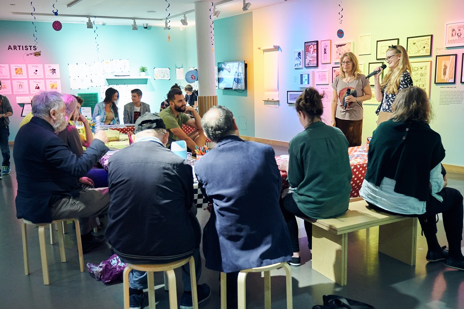 A group of people sitting down and listening to a curator's tour in the Cartoons exhibition at the Jewish Museum London