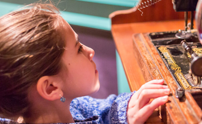 Child playing with sewing machine in the History Gallery