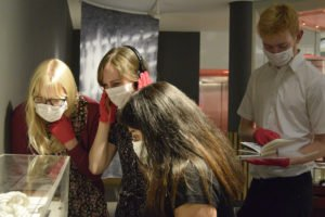 People wearing surgical masks and looking in exhibition vitrines