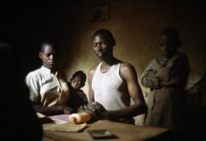 A dark skinned and haired man, two women and a baby looking at a bottle and papers on a wooden table.