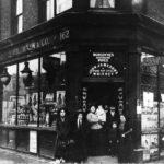The Frumkin family: The Frumkin family standing outside their kosher wine and spirits shop on the corner of Commercial Road and Cannon Street Road, c.1912.