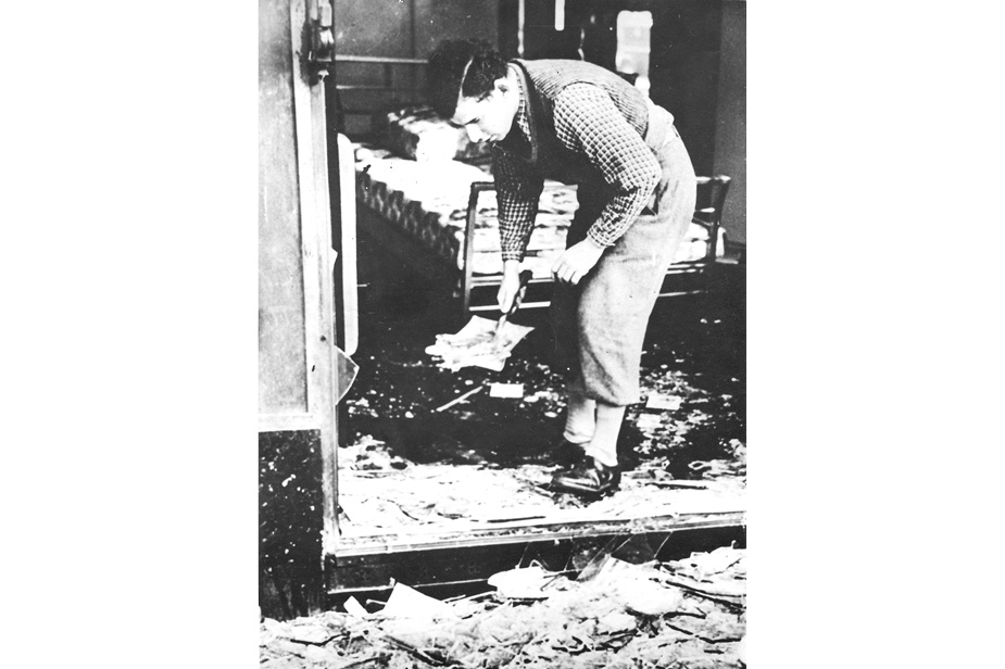 Black and white photograph of adult male bending down to sweep up glass and rubble from vandalised shop doorway
