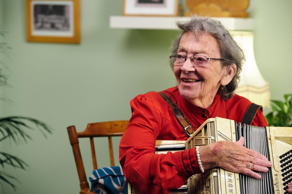 Bea Green, elderly lady, holding an accordian and smiling