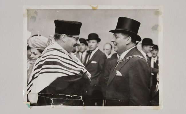 Two men greeting each other in formal clothes