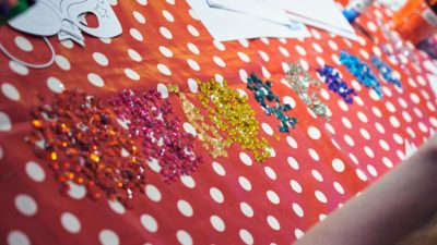 Table with polka dot cover and piles of glitter craft gems