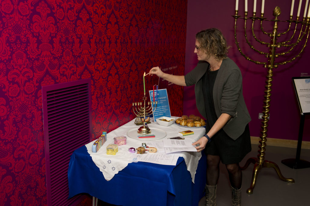 A woman lights a Hanukah candle on a table