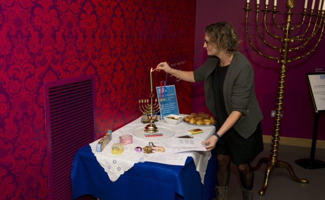 A woman lights a Hanukah candle on a table