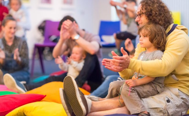 Parent and child clapping and singing at family activity at the Jewish Museum London