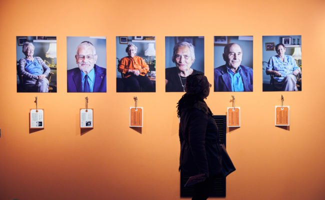 A visitor looks on at 6 colour photographic portaits of the Kindertransport survivors against an orange background